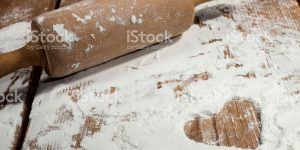 Kitchen rolling pin and with flour on wooden background.